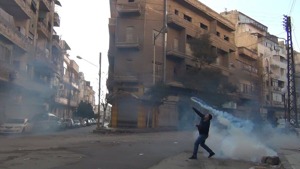 Protester throws tear gas at security forces at a demonstration in the city of Homs (December 2011)