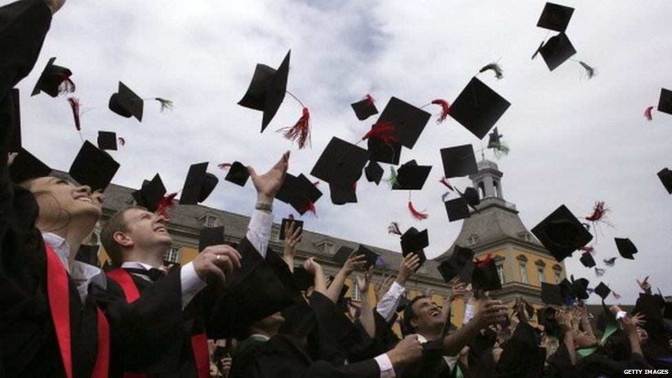 Crowd of graduates throwing their hats in the air
