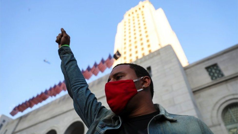 A man raises his fist as demonstrators gather in front of Los Angeles City Hall