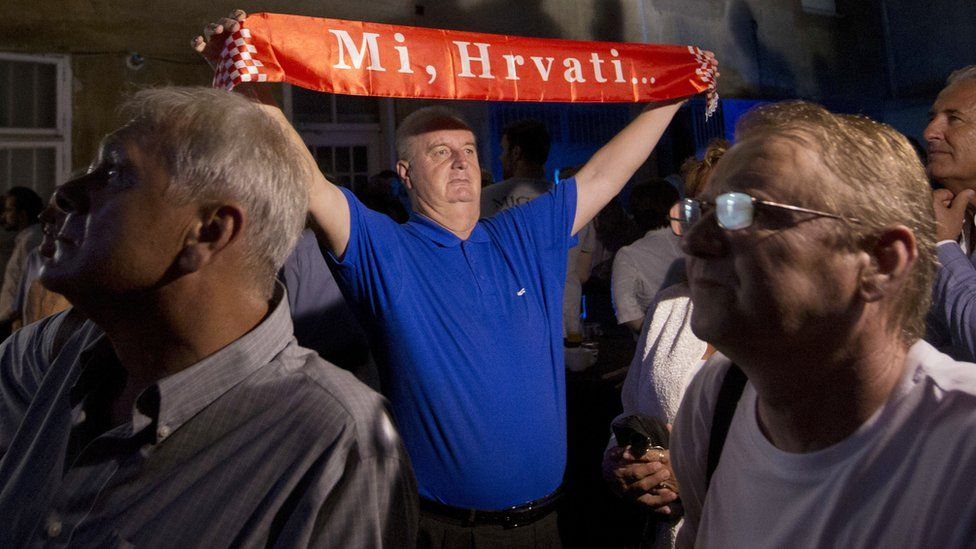 """HDZ supporter with banner reading """"We, Croats!"""""""