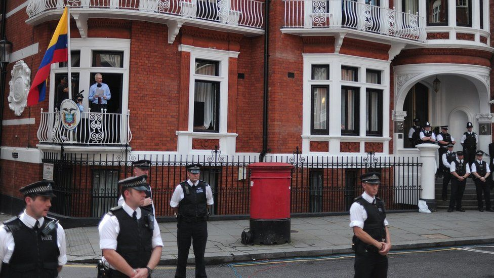 Police officers stand guard as Wikileaks founder Julian Assange addresses the media and his supporters from the balcony of the Ecuadorian Embassy in London, 19 August 2012