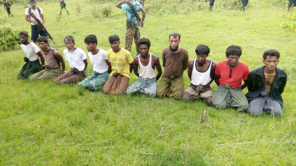 Ten Rohingya Muslim men with their hands bound kneel as members of the Myanmar security forces stand guard in Inn Din village, taken Sept 2017