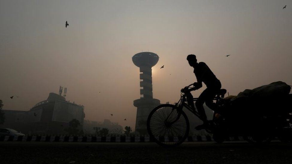 A rickshaw puller passes in front of a shopping mall amidst the heavy smog in New Delhi, India, October 31, 2016