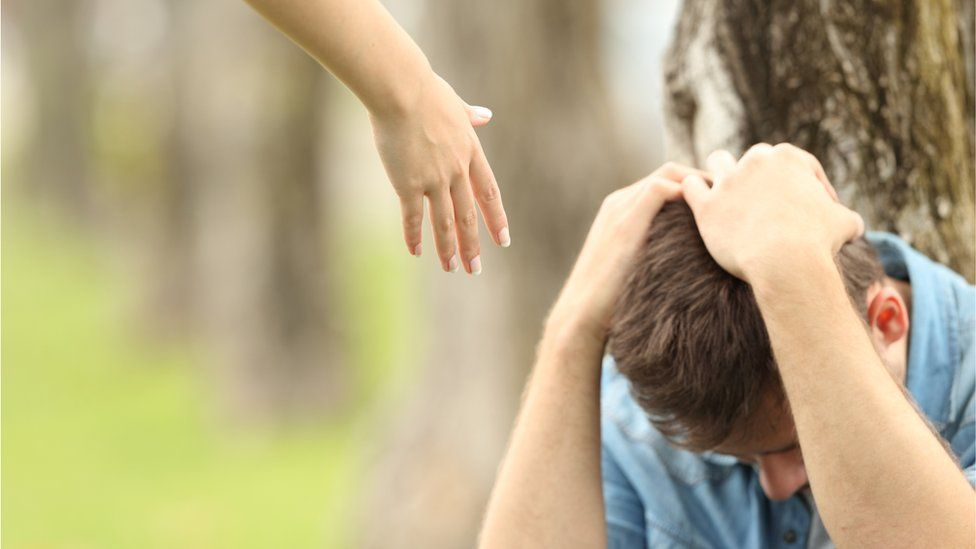 A hand reaches down to a teenager sitting with his head in his hands
