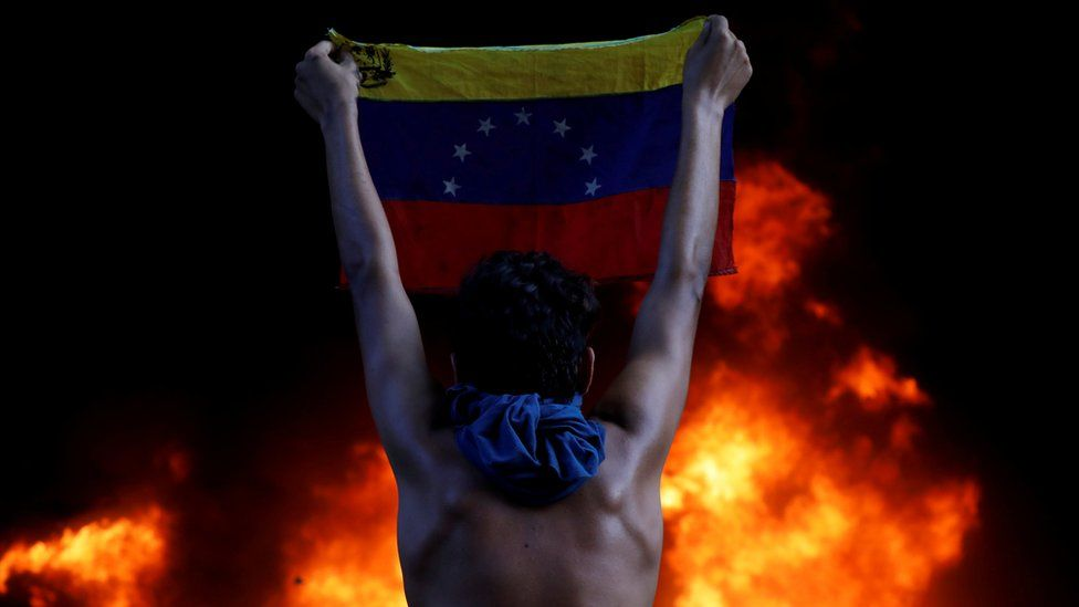A protestor holds a national flag while standing in front of a fire burning at the entrance of a building housing the magistracy of the Supreme Court of Justice and a bank branch.