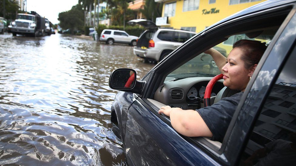 Sandy Garcia sits in her vehicle that was stuck in a flooded street caused by the combination of the lunar orbit which caused seasonal high tides and what many believe is the rising sea levels due to climate change on September 30, 2015 in Fort Lauderdale, Florida