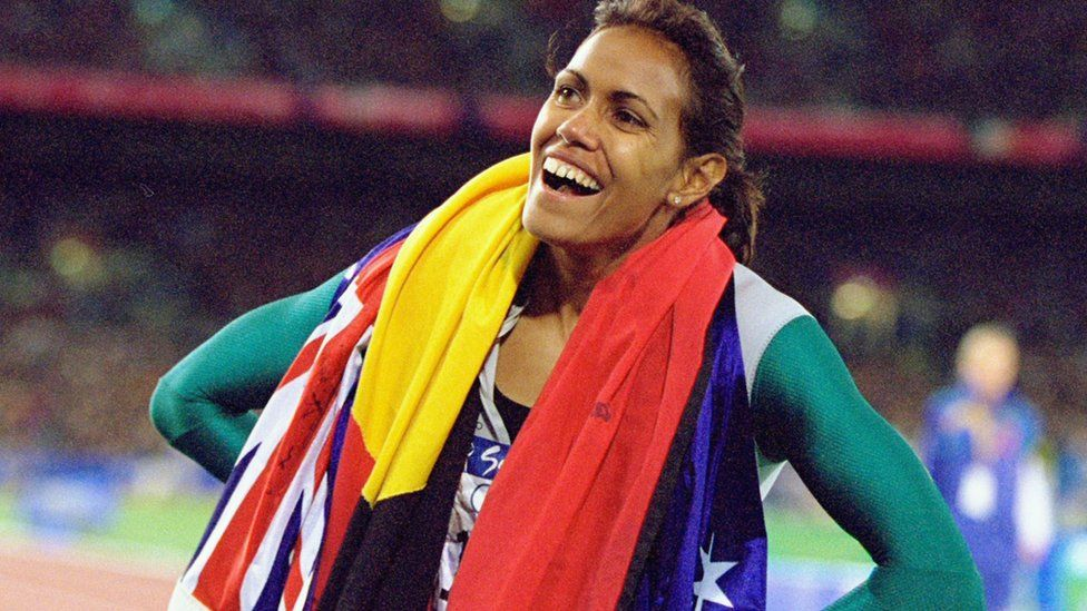 Cathy Freeman wearing the Aboriginal and Australian flags after her win at the Olympics in 2000