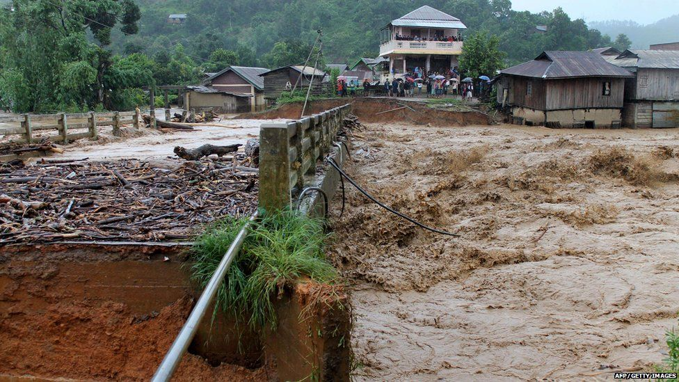 People look at the bridge which was washed away by the floodwaters in Thoubal District in Manipur state on August 1, 2015.