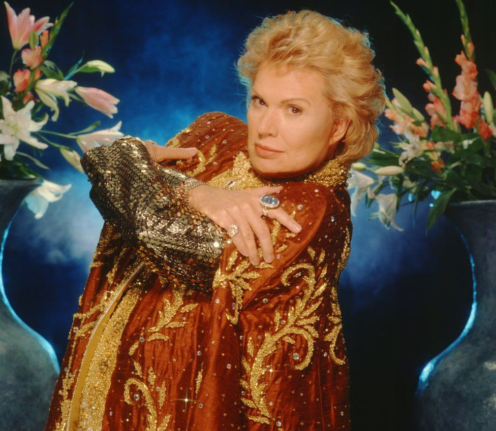 Walter Mercado poses with his hands crossed over his chest, in a sequinned orange and gold robe