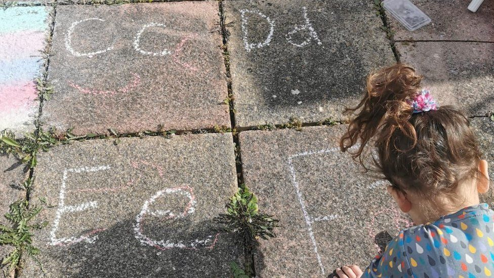 A child drawing letters with chalk in a garden