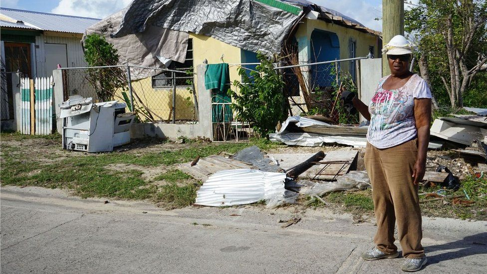A Barbudan woman, Princess Harris-Parker, stands in front of a house covered in tarpaulin