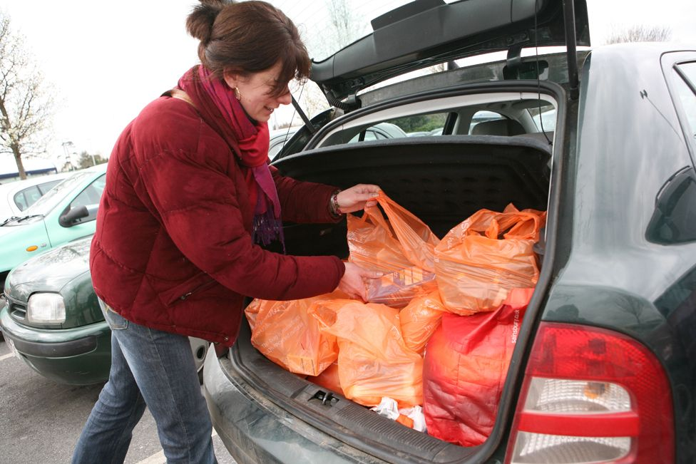woman puts bags in car boot