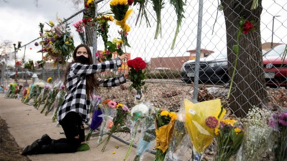 A teenage girl leaves flowers at the site of a mass shooting at King Soopers grocery store in Boulder Colorado