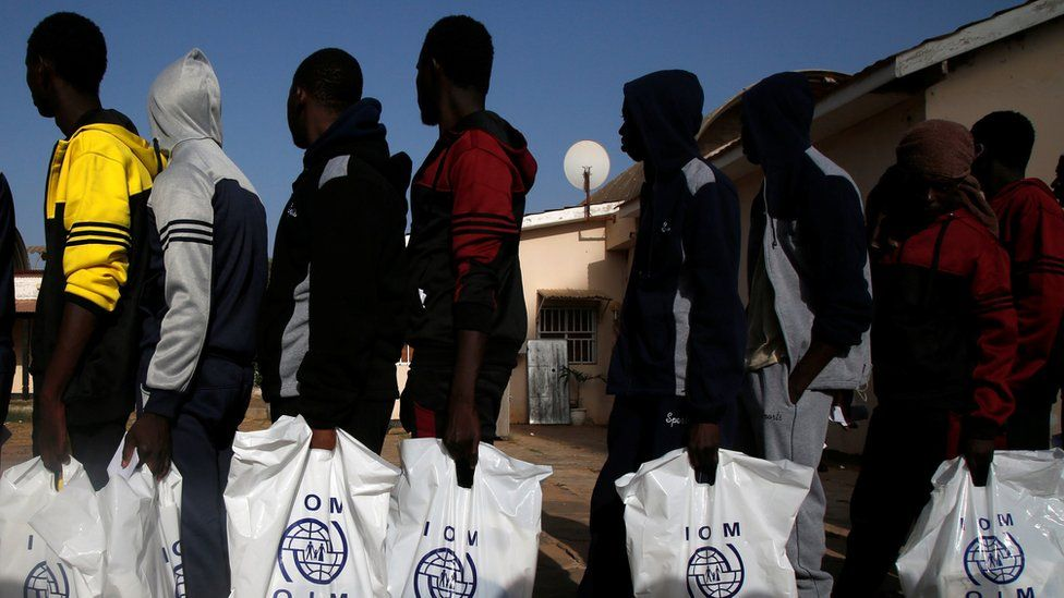 Gambian migrants who returned voluntarily from Libya stand in line with plastic bag from the International Organization for Migration (IOM) as they wait for registration at the airport in Banjul, Gambia April 4, 2017
