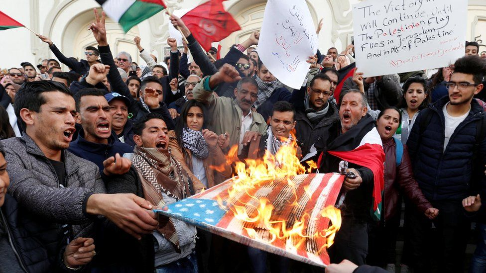 Protesters burn a US flag in Tunis, Tunisia - Thursday 7 December 2017