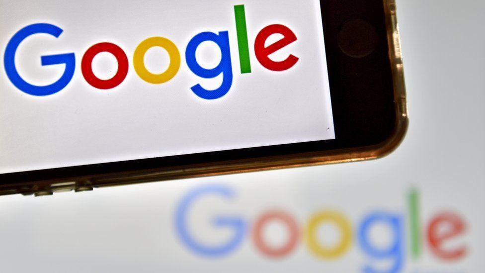 A Google company logo appears on a smartphone