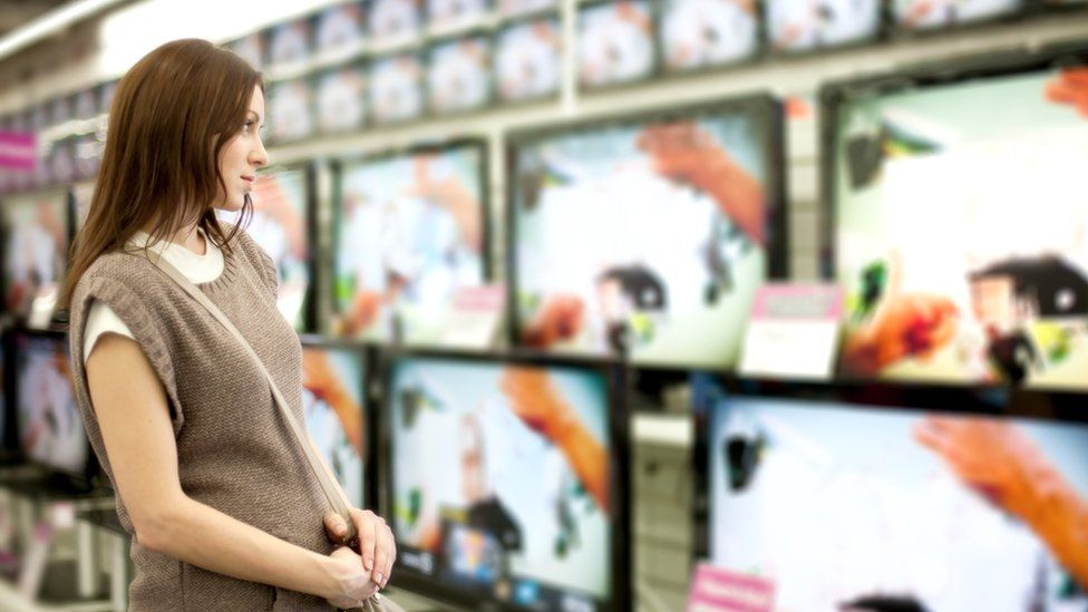Woman looking at TVs for sale