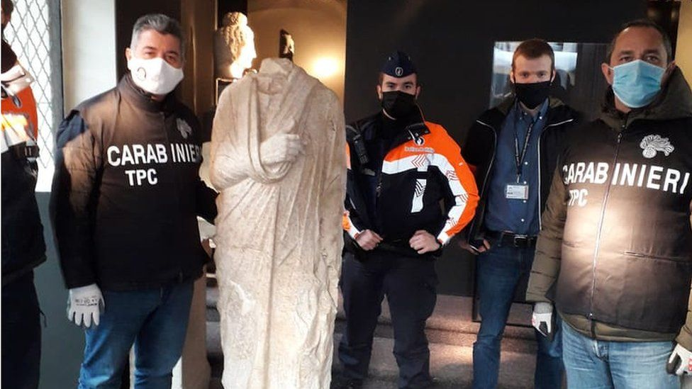 Carabinieri officers pose with the recovered statue