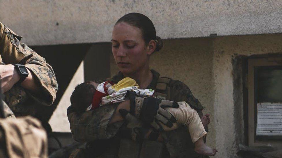 US Marine Sgt Nicole Gee, holding an Afghan baby