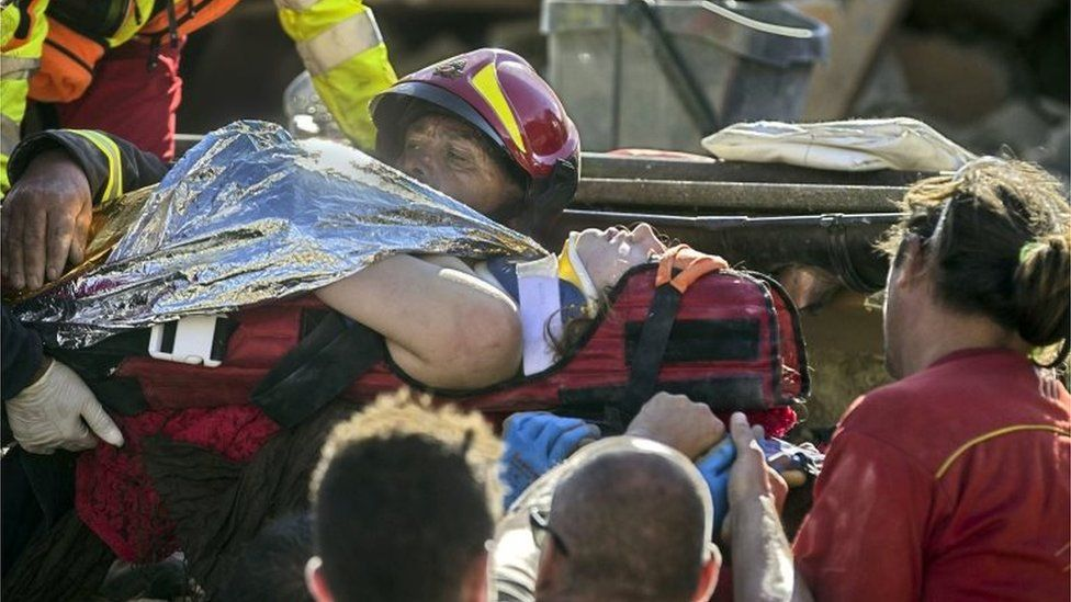An injured woman is carried by rescuers in Amatrice, central Italy, where a 6.1 earthquake struck, Italy (24 August 2016)