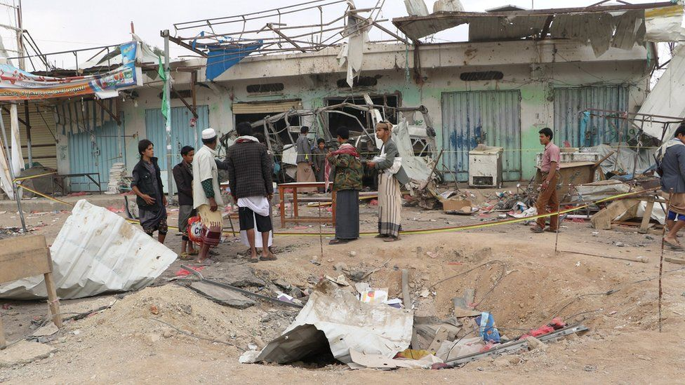 People stand at the site of an air strike on a bus in Dahyan, Saada province, Yemen (10 August 2018)