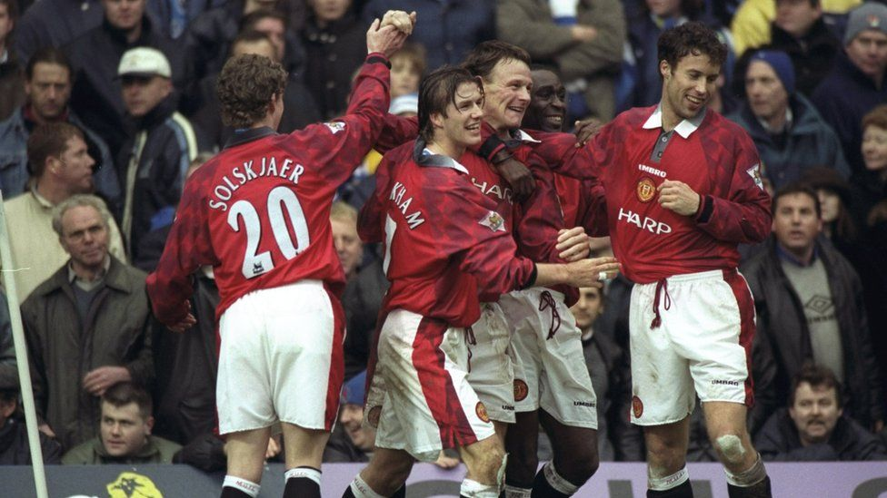 Teddy Sheringham and Andy Cole celebrate with their Manchester United team-mates