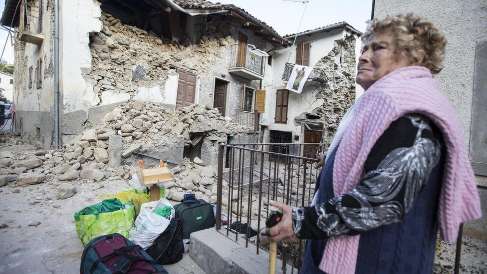 Woman stands next to rubble in Accumoli