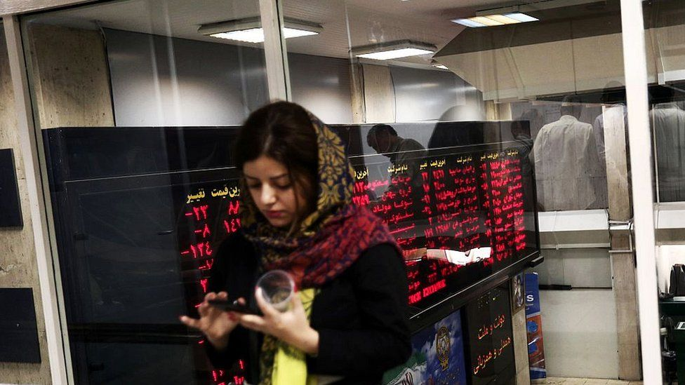 An Iranian woman uses a mobile phone next to a stock market activity board at the stock exchange in the capital Tehran