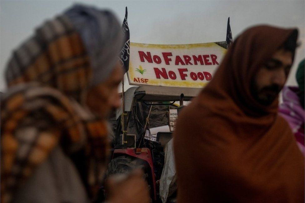 Farmers stand next to a fire as they warm themselves on a cold winter morning at the site of a protest against new farm laws, at Singhu border, near New Delhi, India, DecemberIMAGE COPYRIGHTREUTERS