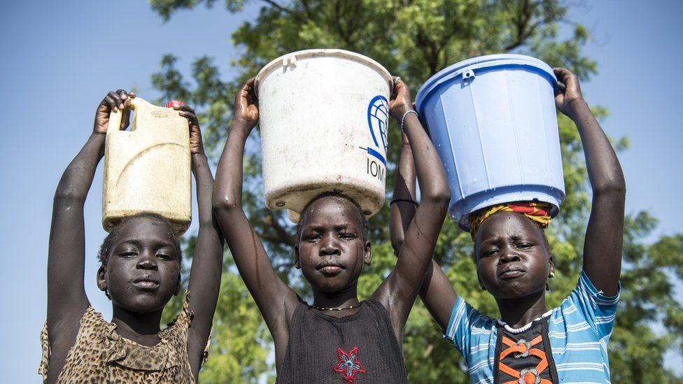 Girls, each carrying a container of water on her head, stand outdoors in the city of Bentiu, capital of Unity State on June 2, 2016.