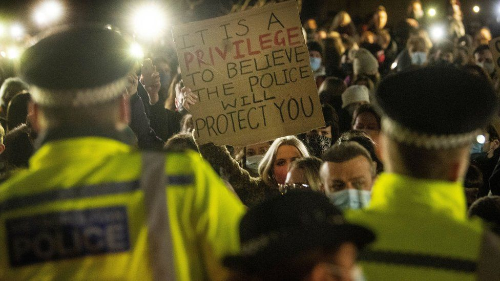 A woman holds up a placard as people gather in Clapham Common
