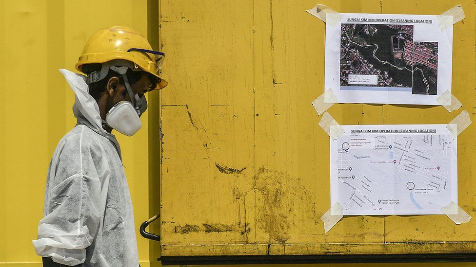 An emergency worker passes by maps displaying cleaning locations of the site