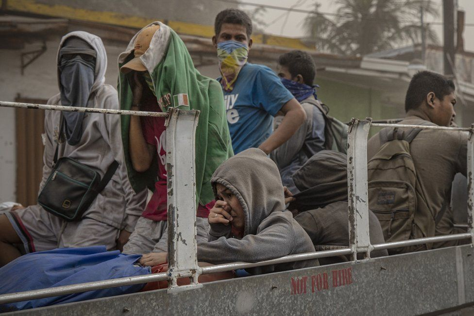 """Residents fleeing Taal Volcano""""s eruption ride a flatbed truck on January 13"""