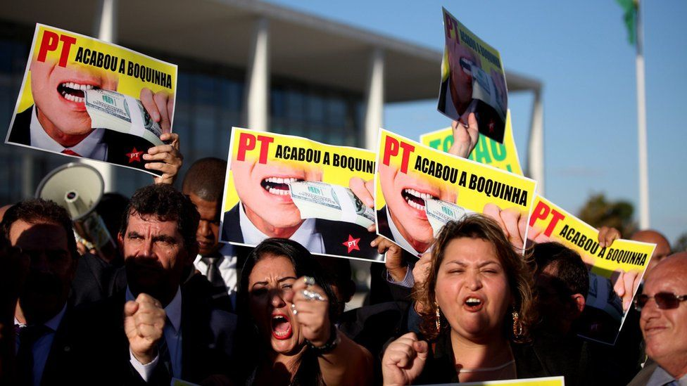 """Deputies and activists holding placards that read """"PT the snacking has ended"""" during a protest against Dilma Rousseff in Brasilia (12 April 2016)"""