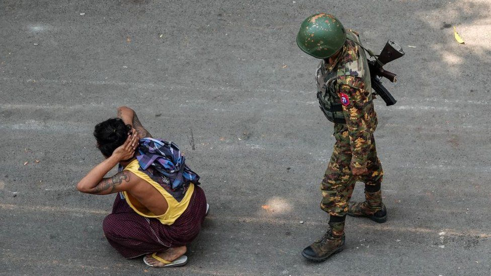 Myanmar soldier with arrested civilian