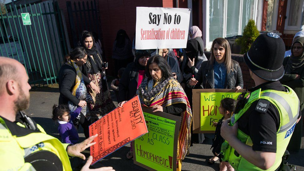 """Police and parents at a protest outside a school. A placard reads """"Say no to sexualisation of children"""""""