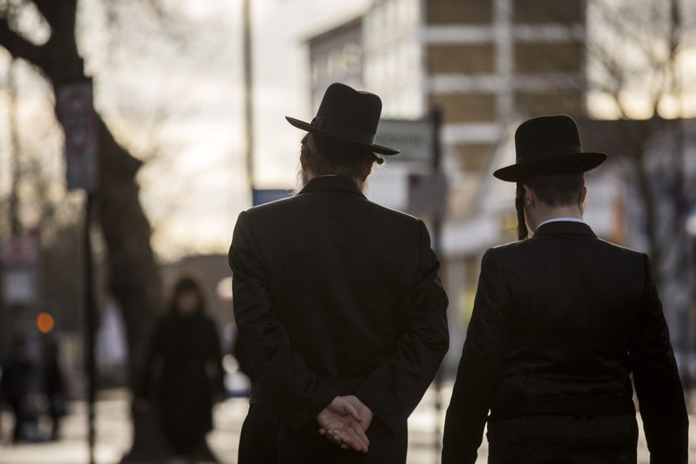 Two Jewish men, photographed from behind, walking along a street in London's Stamford Hill area