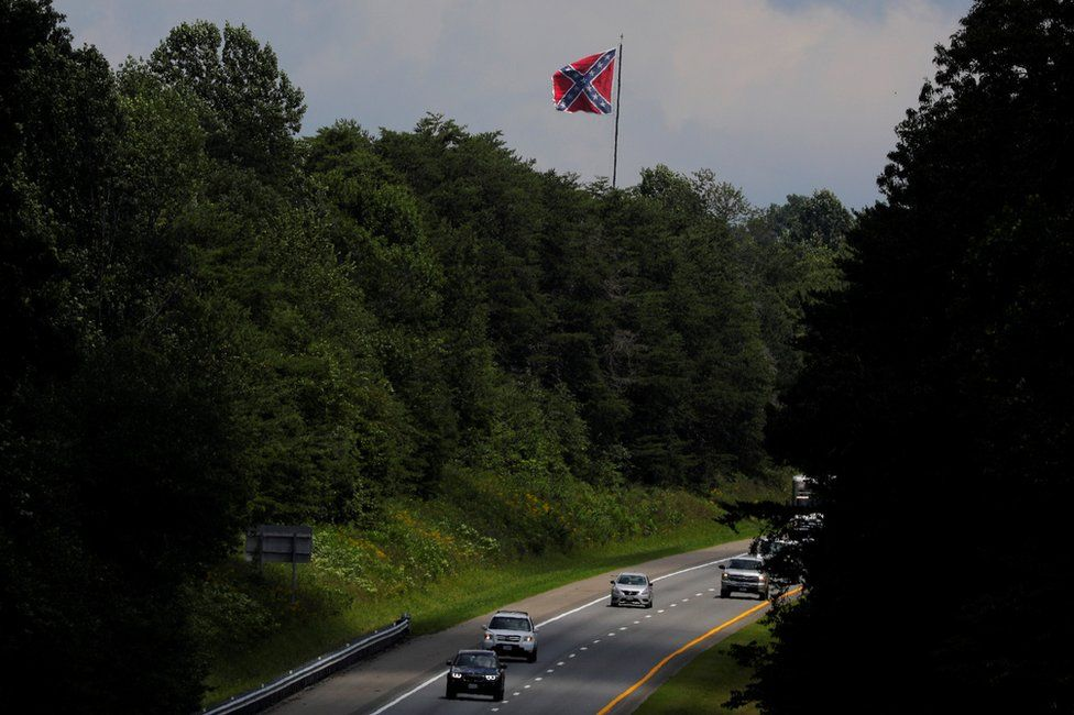 A Confederate battle flag flies over the I-64 highway, outside Charlottesville, August 1, 2018