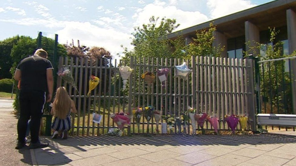 Floral tributes pinned to school fencing