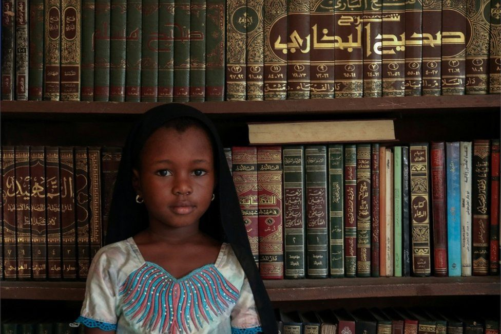 Kadiatou Diallo poses next to religious books during the first day of the Mulsim holy month of Ramadan, in Abidjan, Ivory Coast on 24 April.