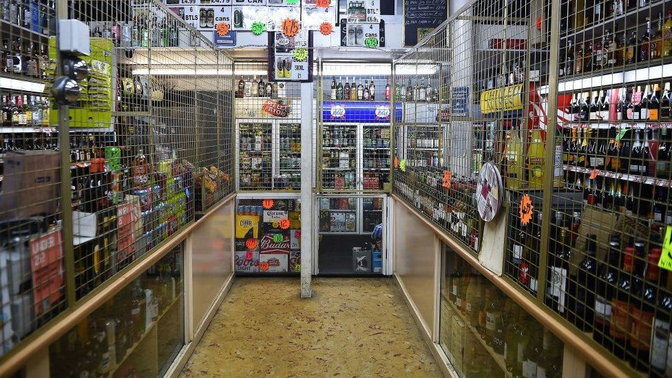 A interior of a liquor store displaying bottles and cans with price tags is pictured in Glasgow on November 1