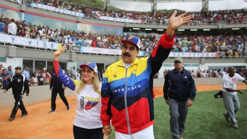 Nicolás Maduro waves to the crowd while walking next to his wife Cilia Flores