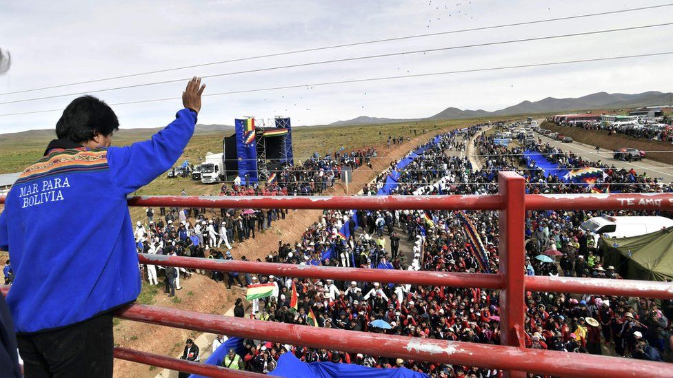 Handout picture released by the Bolivian presidency press office showing President Evo Morales waving to the crowd during the unfolding of a huge 200km flag