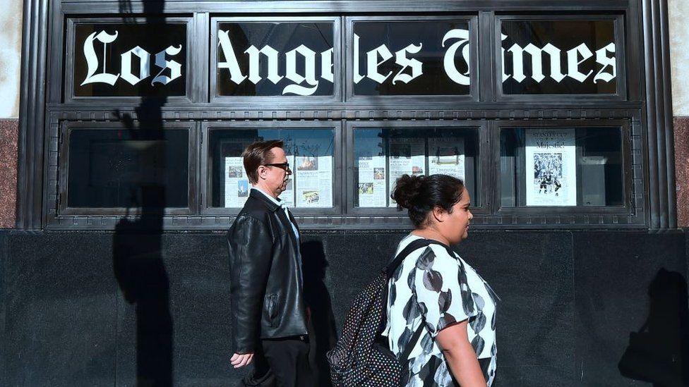 People walking past LA Times building in LA
