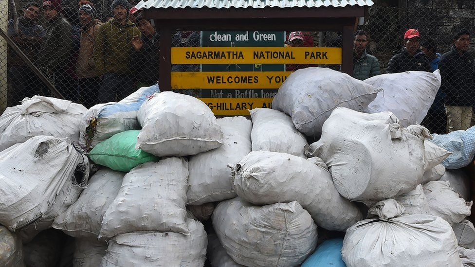 """Locals look at piles of rubbish bags lying against an airport fence next to a sign reading """"clean and green: Sagarmatha National Park Welcomes You"""""""