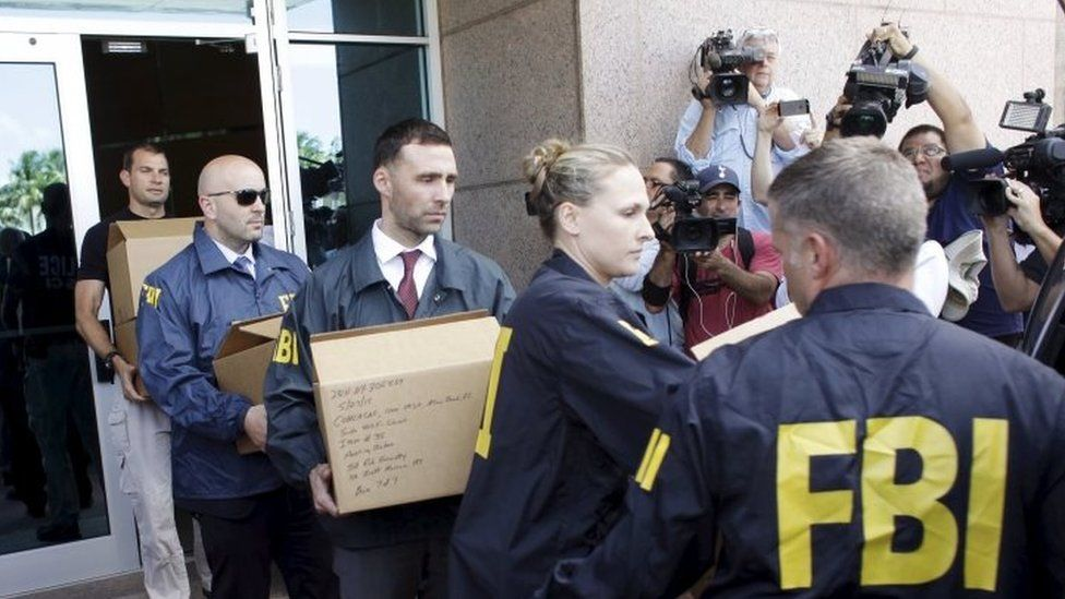 FBI agents carry boxes and computers from the headquarters of Concacaf after it was raided on 27 May in Miami Beach, Florida