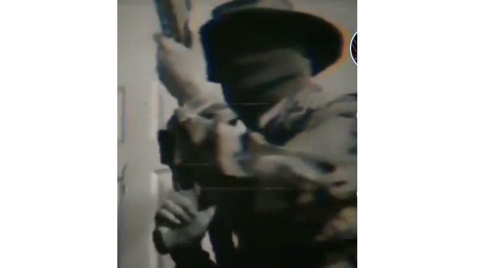 Screengrab from Tiktok showing a man with a large gun and using a Boogaloo hashtag