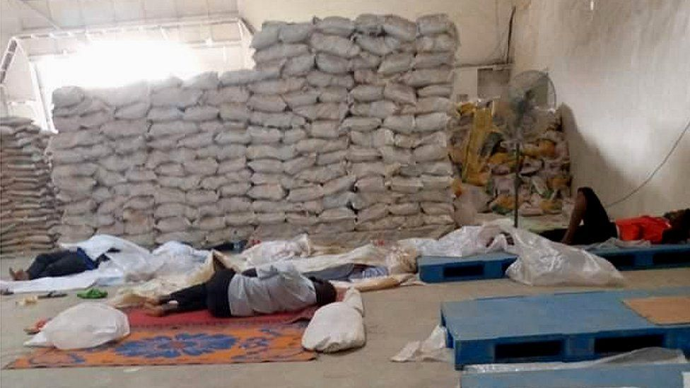 Men sleeping on the floor in a rice mill