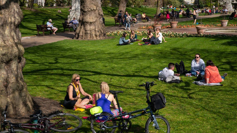 People relax in the sun at Victoria Embankment Gardens, Central London