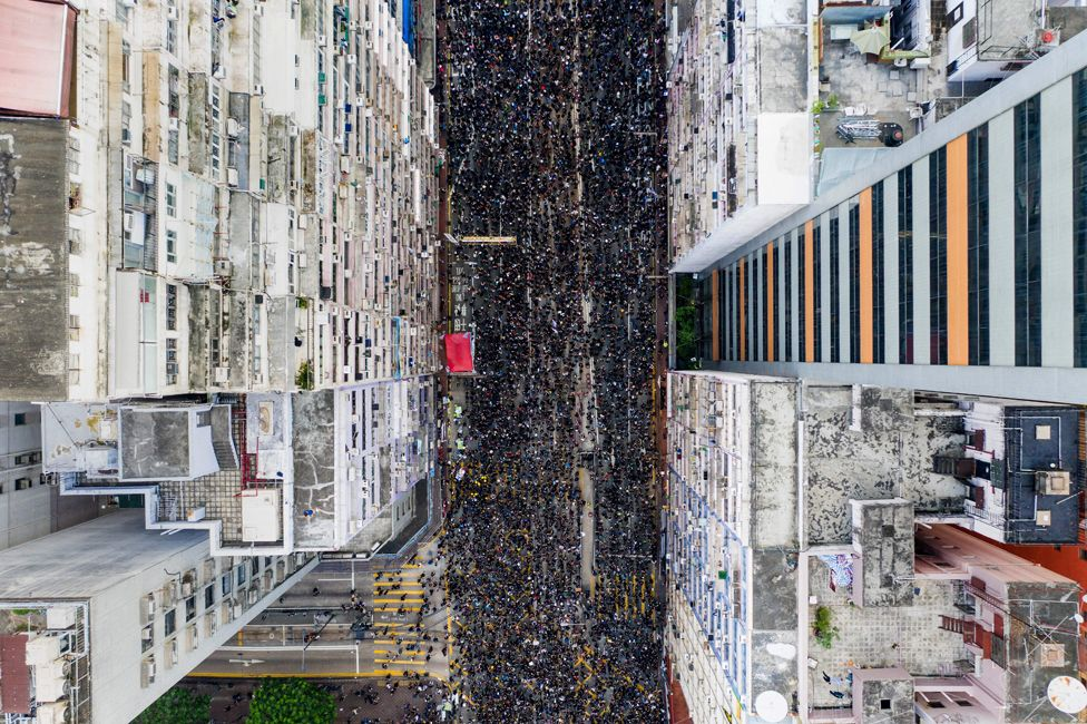 Overhead view shows thousands of protesters marching through the street as they take part in a new rally against a controversial extradition law proposal in Hong Kong on 16 June 2019